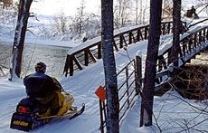 Snowmobile Crossing a Bridge