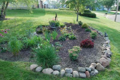 A rain garden with flowers and plants and a rock perimeter
