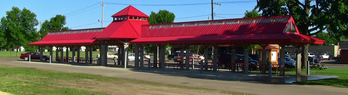 A large, covered picnic area with a bright red roof
